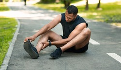 Sports injury. African American runner sitting on jogging track and feeling pain in his ankle, panorama