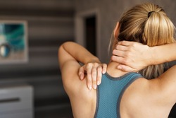 Sports injury concept. Athletic woman feeling pain in her neck against blurred background. Pain after home workout