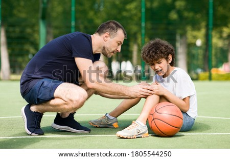 Sports Injury. Handsome PE teacher helping boy with knee trauma after playing basketball Stockfoto ©