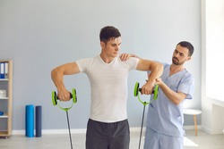 Sports injury rehabilitation. Male athlete doing exercise with resistance elastic rubber band. Physiotherapist helping serious young sportsman restore arm muscles and joints after professional trauma