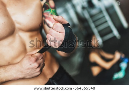 Stock Photo Sports joint . A guy and a girl at the gym . Naked belly - press.Guy tattoo , and the girl is Asian