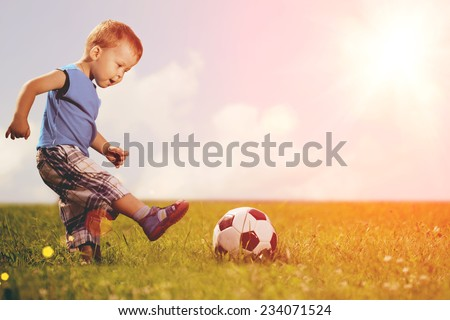 Sports kid. Boy playing football. Baby with ball on sports field. Child plays.