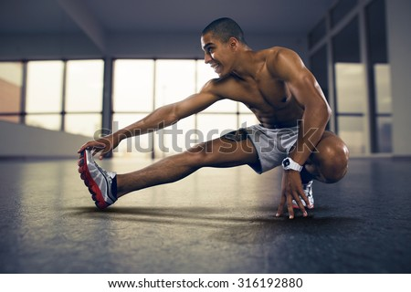 Sports. Man at the gym doing stretching exercises and smiling on the floor