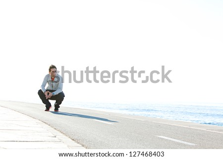 Sports man crouching down on running track by the sea, with a blue sky in the background on a sunny day, being thoughtful.