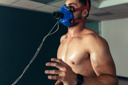Sports man running on treadmill and monitoring his fitness performance. Male runner wearing mask on treadmill in sports science laboratory.