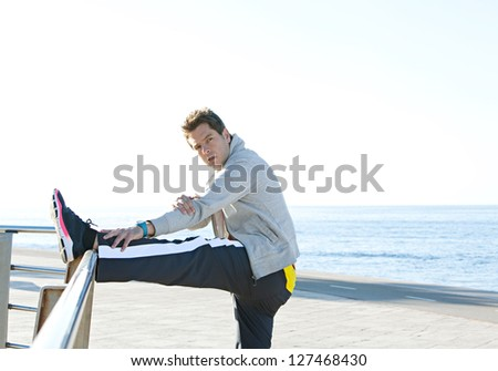Sports man stretching his legs while exercising by the sea side, with a blue sky and ocean in the background, outdoors.