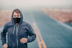 Sports mask endurance athlete runner running outside on road training while wearing facial covering in cold weather winter fog. Male jogger man jogging.