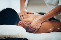 Sports massage. Massage therapist massaging shoulders of a male athlete, working with Trapezius muscle. Toned image