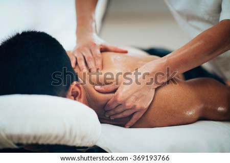 Photo of Sports massage. Massage therapist massaging shoulders of a male athlete, working with Trapezius muscle. Toned image