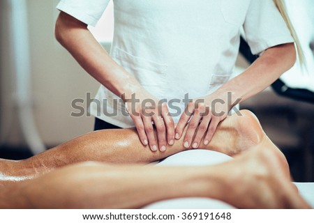 Sports Massage. Massage therapist working with patient, massaging his calves. Toned image.