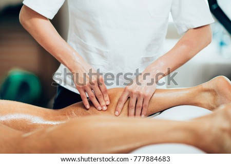 Sports massage. Physical therapyst massaging leg of young male athelete