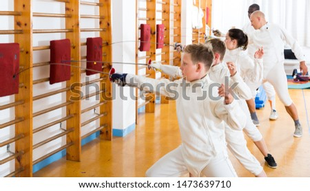 Sports mixed age group of athletes at fencing workout, training attack movements on mannequins #1473639710