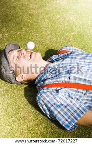 Sports Nut Is A Golfer Man Lying Down On A Golf Course Laughing With A Huge Smile While Balancing A Golf And Tee In His Moth In A Sport Concept