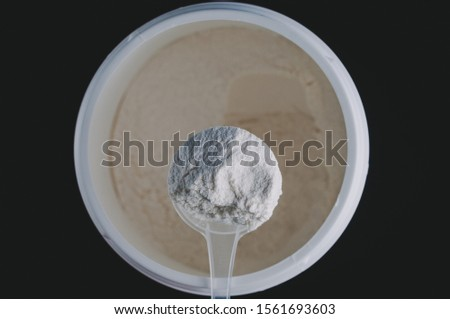 Sports Nutrition Powder. Soluble bcaa in a measuring spoon in the hand to increase the endurance and strength of the athlete. On a black background, isolate.