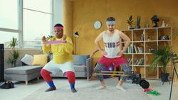 Sports parody. Comical funny unfit retro looking young men training with resistance bands doing wrong exercises having fun home workout.