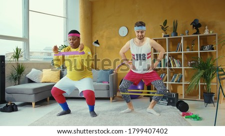 Sports parody. Comical funny unfit retro looking young men training with resistance bands doing wrong exercises having fun home workout. Foto stock ©