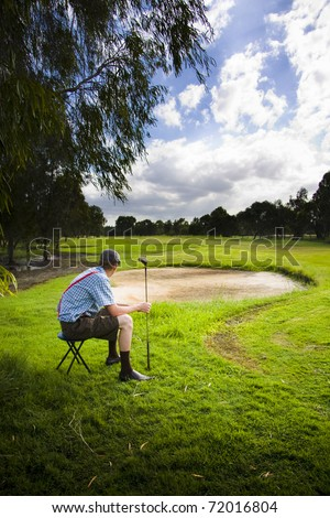 Sports Player Sits On A Beautiful Green Golf Course Fairway In The Early Morning Holding His Golfing Stick In Anticipation For A Fun Sunny Round Of Golf