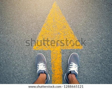 Sports shoes on road with yellow arrow line and vintage tone. soft focus  #1288665121
