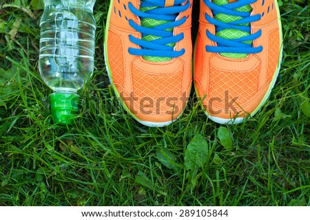 Sports shoes sneakers and bottle of water on a fresh green grass. Sport equipment top view. Sports in the open air. #289105844