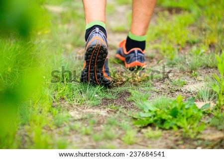 Sports shoes walking or jogging on green grass, man runner cross country running on trail in summer forest. Athlete male training and doing workout outdoors in nature. Jogging workout fitness concept. #237684541