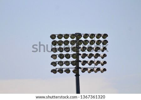 Sports stadium floodlights at day with blue sky #1367361320