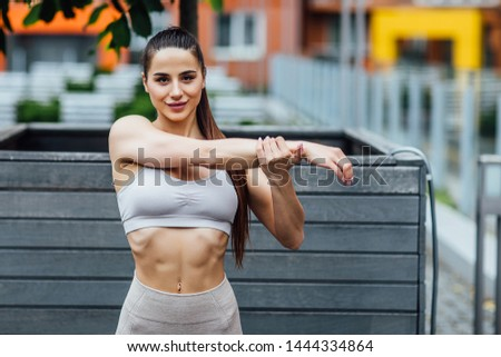 Sports, strenght, determination ad endurance concept. Outdoor shot of confident young sportswoman dressed in running outfit stretching arms before physical workout.