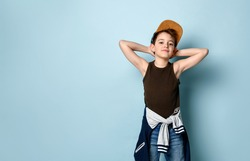sports-style guy is standing, looking at you and holding a cap on his head. Childhood, naughty, troublemaker. Studio shot isolated on blue background. Copy space.