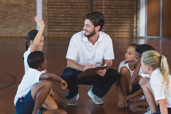 Sports teacher having discussion with his students in basketball court at school gym