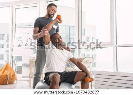 Sports therapy. Pleasant good looking man exercising with dumbbells while being in the gym #1070432897