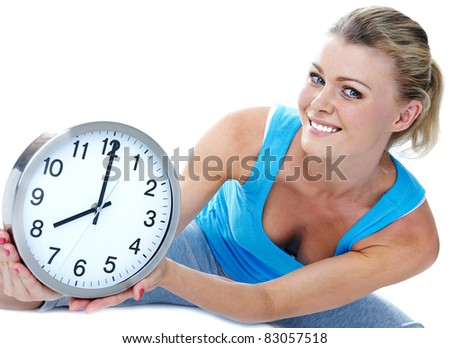 Sports time. The girl in sportswear with a big clock in hands