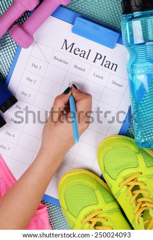 Sports trainer amounts to meal plan and sports equipment top view close-up