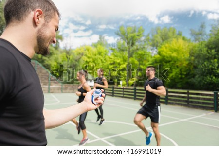 Sports trainer with stopwatch, cardio training outdoors