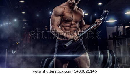 Sports training for endurance, man hits hammer. Concept workout