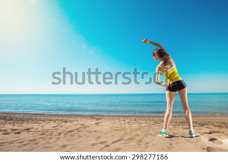 Sports training on the beach. Young sports woman stretching. Healthy lifestyle outdoors.