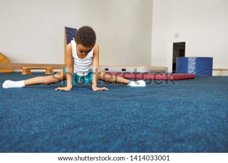 Sports, wellbeing, health and active lifestyle concept. Picture of unrecognizable flexible African American boy in shorts, white socks and A-shirt stretching on mat at gym, doing side splits