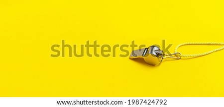 Sports whistle on yellow background. Concept- sport competition, referee, statistics, challenge. Basketball, handball, futsal, volleyball, soccer, baseball, football and hockey referee whistle