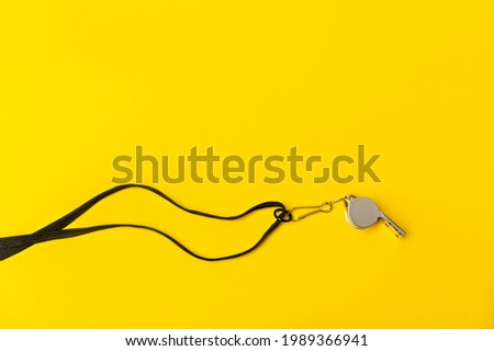 Sports whistle on yellow background. Concept - sport competition, referee, statistics, challenge. Basketball, handball, futsal, volleyball, soccer, baseball, football and hockey referee whistle