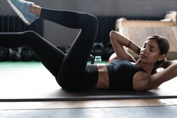 Sports woman doing bicycle crunch workout at gym. Female in the gym doing abs workout exercise at fitness club
