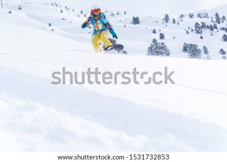 Sports woman in helmet and mask is riding on snowboard on snowy slope at winter day. #1531732853