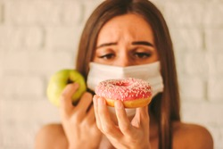 Sports woman in protective mask on face deciding between healthy food or sugar snack. Fitness girl in medical face mask hold apple and donut in hands. Diet, healthy lifestyle, coronavirus quarantine