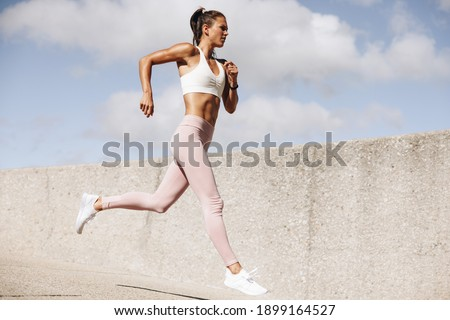 Sports woman running outdoors in the morning. Female athlete in running attire exercising in morning.