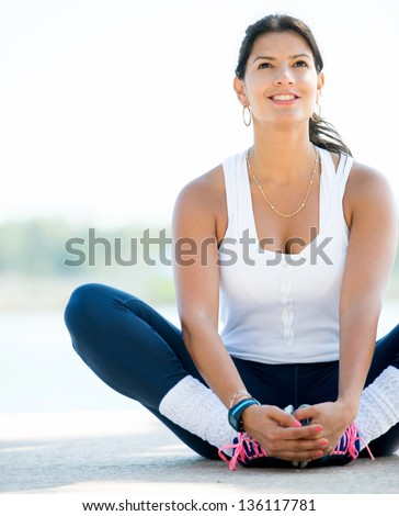 Sports woman stretching her legs outdoors before exercising