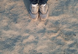 Sports women's light gray sneakers on wet sand with shadows from the setting sun. The concept of evening or morning jogging, fitness and workout. Top view, copy space.