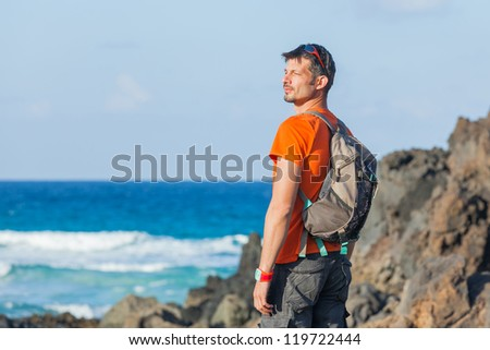 Sports young man with backpack. Background of the sea