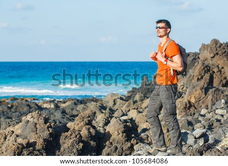 Sports young man with backpack. In the background of the sea