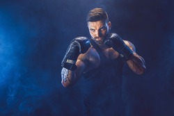 Sportsman boxer fighting on black background with shadow. Copy Space. Boxing sport concept. Smoke on background