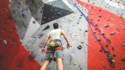 Sportsman climber is looking on steep rock, climbing on artificial wall indoors. Extreme sports and bouldering concept