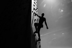 Sportsman climber on steep rock, climbing on artificial wall. Extreme sports and bouldering concept.