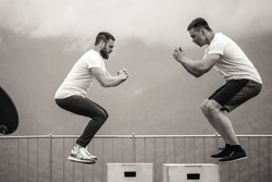 Sportsman fit male jumper doing explosive strength training jumps, crossfit fitness workout strenght power concept . Handsome strong men exercising on sky and mountain background, monochrome.