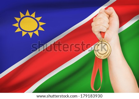 Sportsman holding gold medal with flag on background - Republic of Namibia